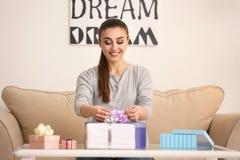 Подарки красивой молодой женщины пакуя дома стоковые изображения rf