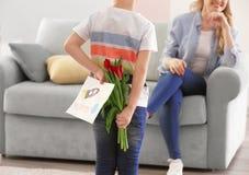 Подарки мальчика пряча для матери за его назад дома стоковые изображения