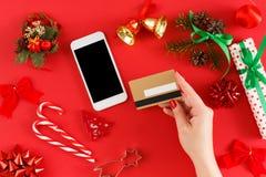 Подарки на рождество девушки покупая онлайн на smartphone с кредитной карточкой Стоковая Фотография