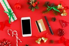 Подарки на рождество девушки покупая онлайн на smartphone с кредитной карточкой Стоковая Фотография RF