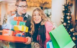 Подарки на рождество и сумки покупок пар в моле стоковое фото
