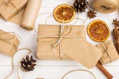 Подарки от бумаги ремесла, высушенного апельсина, циннамона, конусов сосны, анисовки на белой таблице Первоначальное оформление д стоковая фотография