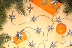 Подарки рождества и Нового Года в оранжевых коробках лежат под рождественской елкой рядом с tangerines и серебристыми звездами Стоковые Изображения RF