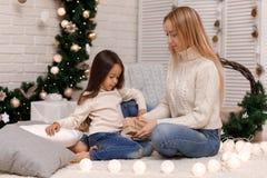 Подарки рождества пакета девушки матери и ребенка дома стоковые фотографии rf
