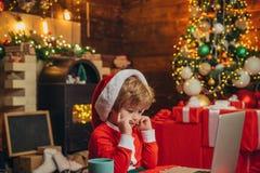 Подарки рождества покупки онлайн Концепция рождества ходя по магазинам Обслуживание подарков Хелпер Санта маленький Умный малыш з стоковое изображение rf