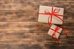 Подарки с красной лентой на деревянном столе стоковые изображения