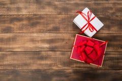 Подарки с красной лентой на деревянном столе стоковые фотографии rf