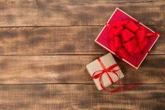 Подарки с красной лентой на деревянном столе стоковая фотография