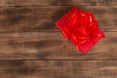 Подарки с красной лентой на деревянном столе стоковое изображение rf