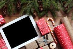 Подарки таблетки и рождества на деревянном столе Стоковое Изображение RF