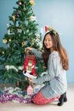 Подарки тайника девушки рождества в носках стоковое изображение