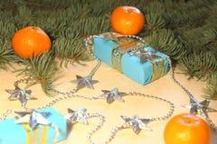 Подарки ` s рождества и Нового Года в голубых коробках лежат под рождественской елкой рядом с tangerines и серебристыми звездами Стоковые Фото