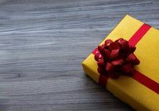 Подарок взгляда сверху желтый на старой предпосылке стоковое изображение