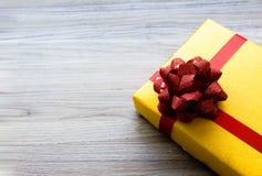 Подарок взгляда сверху желтый на старой предпосылке стоковое фото
