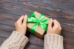 Подарок или настоящий момент с зеленым смычком Руки женщины показывая и давая подарки Крупный план настоящего момента сделанный р Стоковое Изображение RF