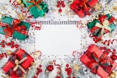 Подарок или присутствующие коробки, пустая тетрадь, снежная ель и украшения рождества на белом взгляде сверху деревянного стола П стоковое фото rf