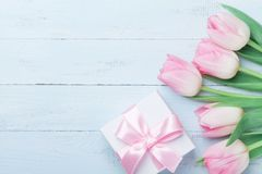 Подарок или присутствующий тюльпан коробки и розовых цветут на голубом взгляд сверху деревянного стола Поздравительная открытка н Стоковые Изображения RF