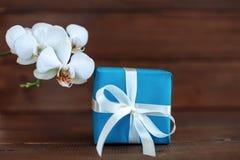 Подарок и орхидея на деревянной предпосылке Концепция торжества Стоковые Изображения RF