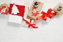 Подарок коробок рождества украшенный с красным цветом обхватывает на белой деревянной предпосылке Плоское положение, модель-макет Стоковое Фото