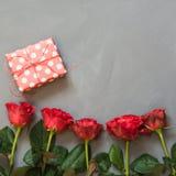 Подарок красной розы и присутствующих на серой предпосылке Валентайн карточки s конец вверх скопируйте космос Стоковые Фото