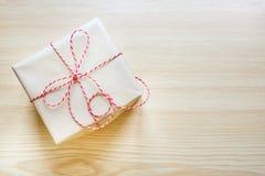 Подарок на рождество обернутый в бумаге ремесла с лентой на деревянной доске Взгляд сверху стоковая фотография rf