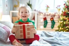 Подарок на рождество ребенка раскрывая стоковые фотографии rf