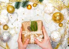 Подарок на рождество с лентой золота и руки украшений рождества золота связывают подарок на рождество Стоковое фото RF