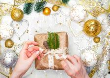 Подарок на рождество с лентой золота и руки украшений рождества золота связывают подарок на рождество Стоковое Фото