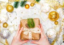 Подарок на рождество с лентой золота и руки украшений рождества золота связывают подарок на рождество Стоковые Изображения