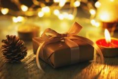 Подарок на рождество на темной предпосылке со светом свечи стоковое изображение