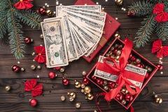 Подарок рождества, деньги упакованные с красной слабиной, деталями Xmas, на деревянной предпосылке Взгляд сверху стоковые фотографии rf