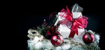 Подарок рождества и красные шарики рождества на черной предпосылке Стоковое Изображение