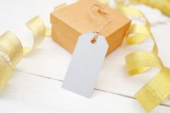 Подарок рождества модель-макета с пустой биркой на белой деревянной предпосылке с лентой золота стоковое изображение rf