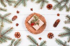Подарок рождества на пне на белой деревянной предпосылке с елью разветвляет, конусы сосны, красные украшения Xmas и счастливый Но Стоковые Фото