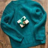 Подарок рождества с зеленой лентой и зеленый свитер на деревянной доске Принципиальная схема рождества Стоковые Фотографии RF