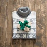 Подарок рождества с зеленой лентой и серый свитер на деревянной поверхности Принципиальная схема рождества Стоковое Изображение
