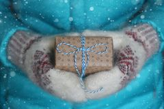 Подарок с голубым смычком в женских руках в шерстяных mittens, текстура снега Стоковые Изображения RF