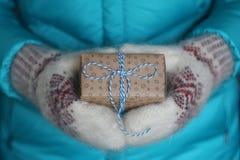 Подарок с голубым смычком в женских руках в шерстяных mittens Стоковые Изображения