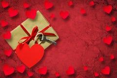 Подарок с ключом и бумажные сердца на красной предпосылке скопируйте космос valentines дня предпосылки счастливые стоковая фотография rf