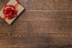 Подарок с красной лентой и смычок на темной деревянной предпосылке Стоковая Фотография RF