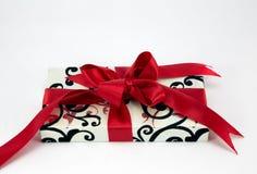 Подарок с красными тесемкой и смычком. Стоковая Фотография