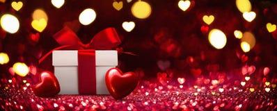 Подарок с сердцами на красной предпосылке стоковое изображение rf