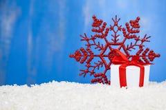 Подарок с смычками и снежинкой красного цвета Стоковые Изображения