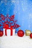 Подарок с смычками красного цвета и снежинка на снеге Стоковое Фото