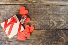 Подарок упакован в бумаге Kraft и связанный с красной лентой поднял Подарок окруженный декоративными сердцами одним обручальное к Стоковая Фотография