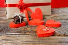 Подарок упакован в бумаге Kraft и связанный с красной лентой поднял Подарок окруженный декоративными сердцами одним обручальное к Стоковые Фото