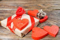 Подарок упакован в бумаге Kraft и связанный с красной лентой поднял Подарок окруженный декоративным сердцем на одном обручальные  Стоковые Фото