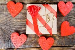 Подарок упакован в бумаге Kraft и связан с красной лентой с розой которая имеет шкентель в форме clogs с гениальным Стоковое Изображение RF
