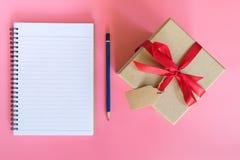 Подарочная коробка взгляд сверху коричневые и бумага тетради на розовом пастельном цвете Стоковые Изображения