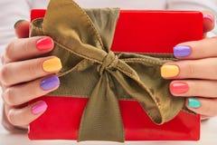 Подарочная коробка в деланных маникюр женских руках Стоковое фото RF